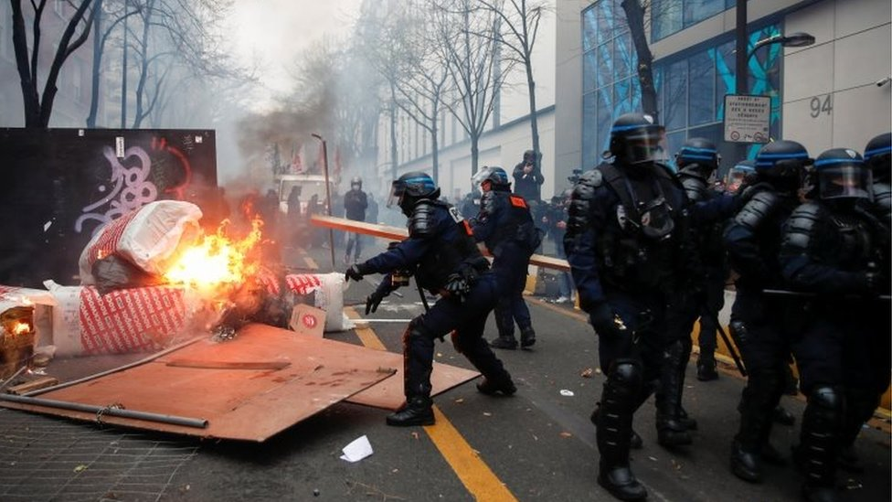 """Police officers remove a barricade during a demonstration against the """"Global Security Bill"""""""", that right groups say would make it a crime to circulate an image of a police officer's face and would infringe journalists' freedom in the country, in Paris, France, on 5 December 2020."""