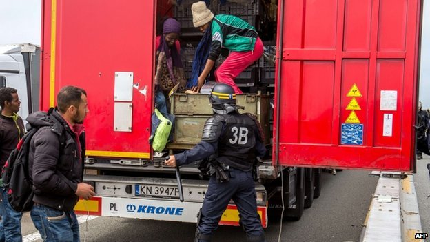 A French policeman stands behind a lorry as migrants climb off the back