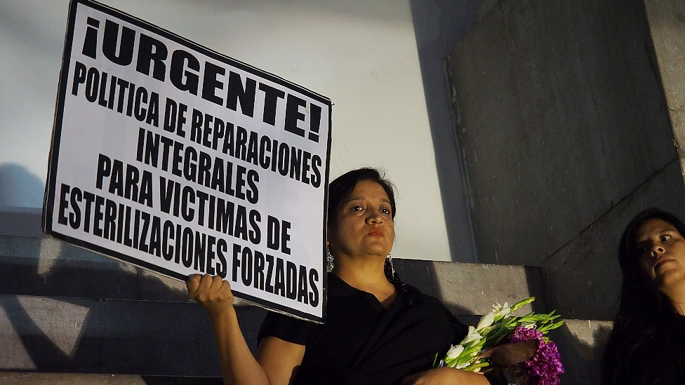 A women holds a sign during a protest demanding compensation in 2017