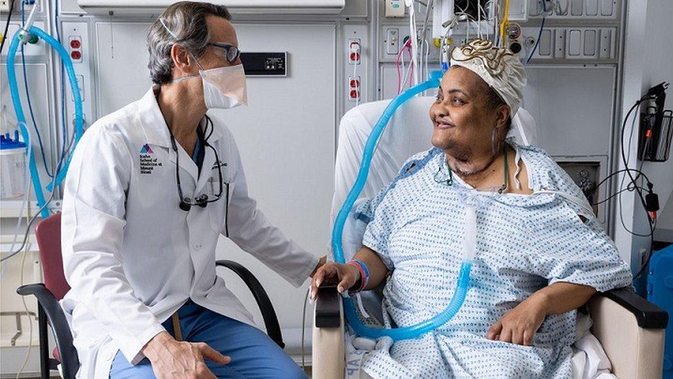 Médico sentado ao lado de paciente em maca, ambos sorrindo e conversando