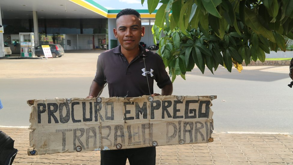 """A man carries a sign reading """"Looking for work"""" in Portuguese around his neck in Boa Vista"""