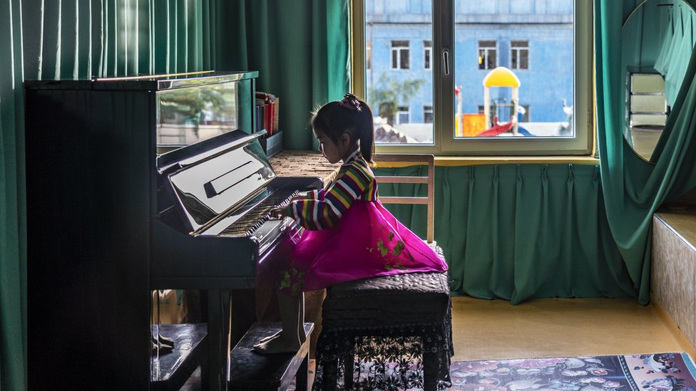 Girl in traditional dress plays the piano