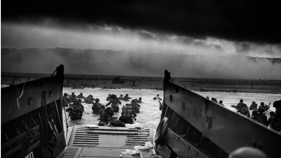 Photograph of U.S Troops rushing to the Normandy Beaches in France during the D-Day landing. Dated 1944.
