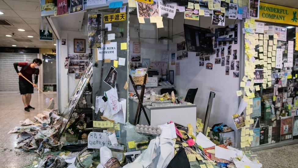 一名黑衣人嘗試打掃被示威者破壞的何君堯立法會議員荃灣辦事處(22/7/2019)