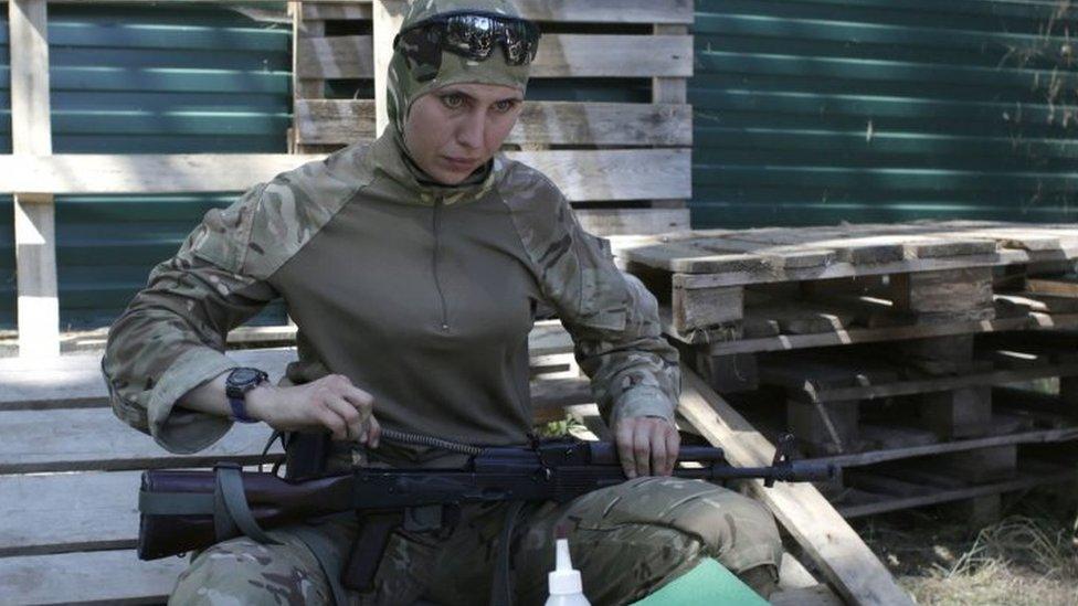 Volunteer fighter Amina Okuyeva cleans her assault rifle. Photo: July 2014