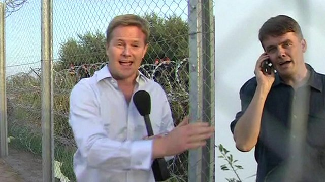 BBC reporter Christian Fraser on the Hungarian side of the border, while James Reynolds (on a mobile phone) reports from the Serbian side.
