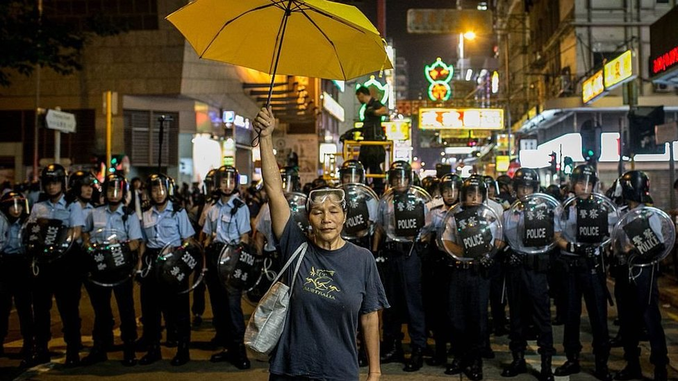 A pro-democracy activist holds a yellow umbrella in front of a police line on a street in Hong Kong in 2014