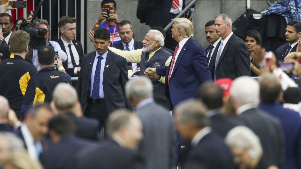 India Prime Minister Narendra Modi and President Donald Trump walk holding hands in Houston, Texas, surrounded by crowds