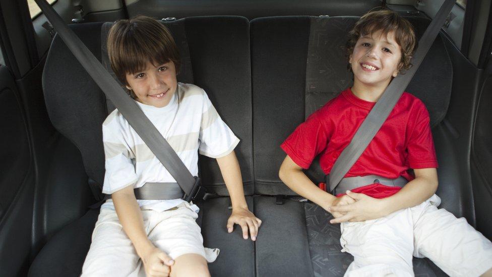 Niños con cinturón de seguridad en el carro