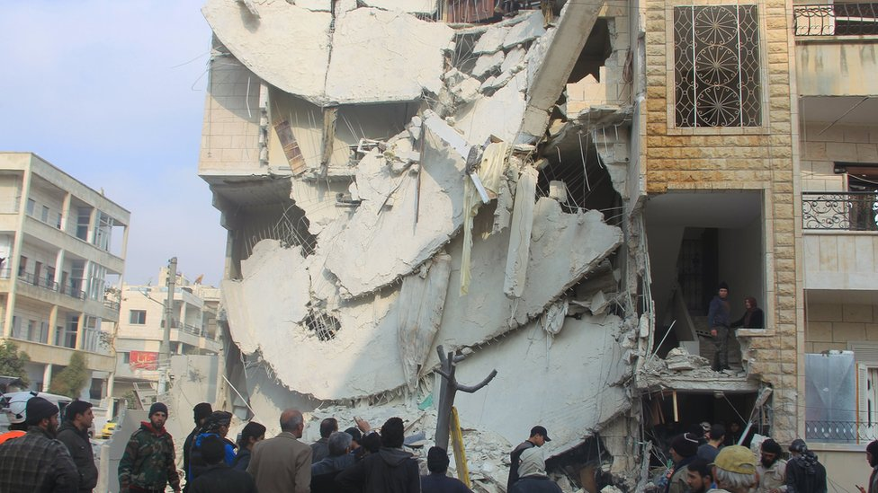 People inspect a site hit by what activists said were airstrikes carried out by the Russian air force in Idlib