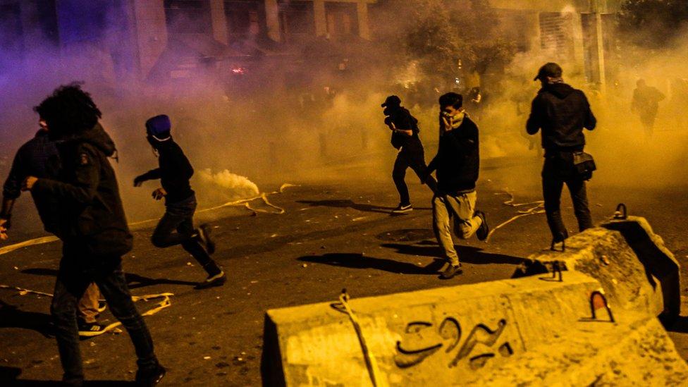 متظاهرون يفرون من دخان قنابل الغاز المسيل للدموع