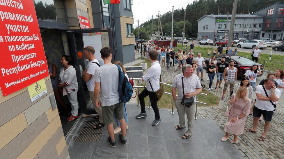 People queue outside a polling station to cast their votes in the presidential election in Barauliany Belarus, August 9, 2020.