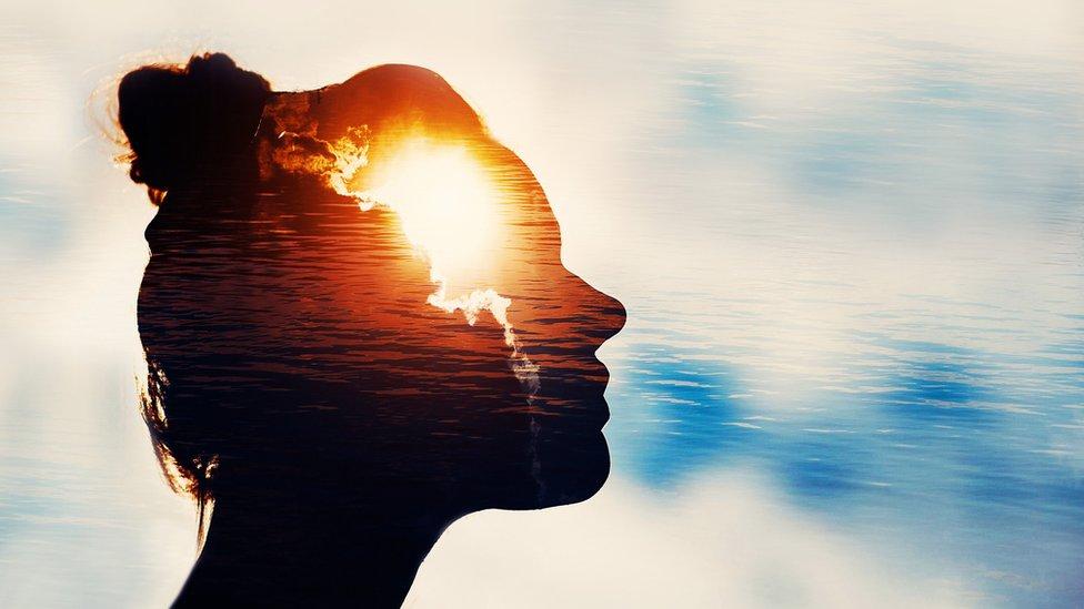 Una mujer en sombra y dentro de su cabeza aparecen rayos de luz