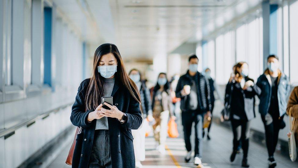 Mulher com máscara segura celular perto de outras pessoas