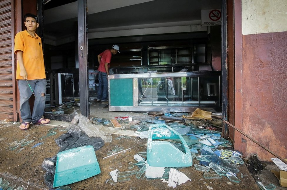 People stand next to broken glass as they look at the damage after a bakery was looted in Ciudad Bolivar, Venezuela, on December 17, 2016.
