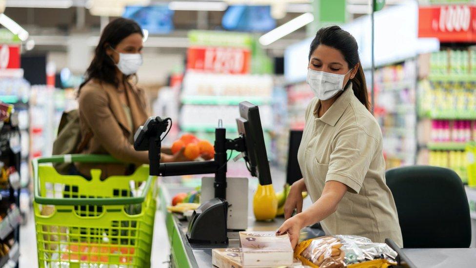 Perempuan bekerja di supermarket, virus corona,covid-19