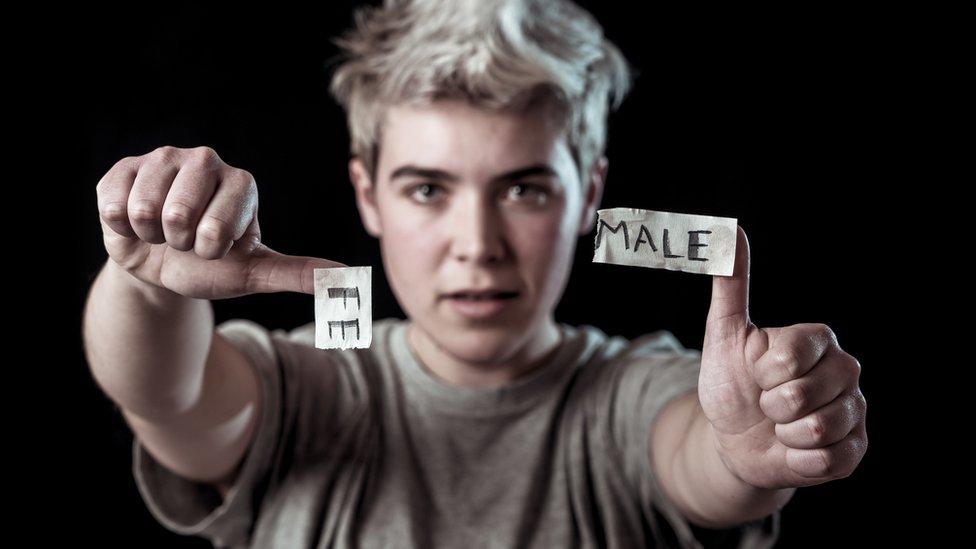 Adolescente transgénero desgarrando la palabra Female en MALE.