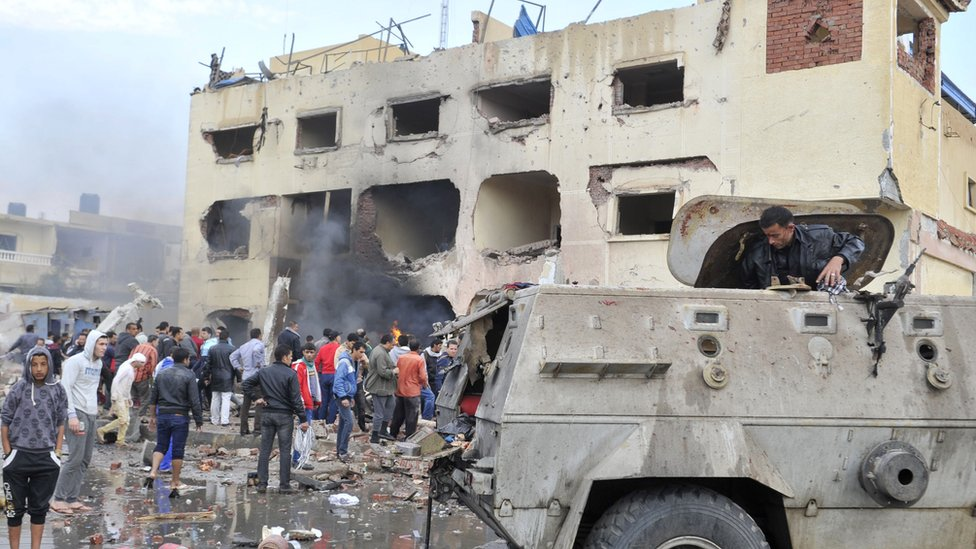The aftermath of a car bomb attack outside a police station in North Sinai's provincial capital of El-Arish