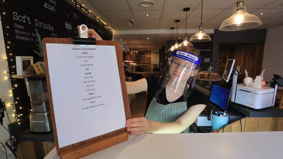 Louisa Ingleton puts out a menu for a free breakfast for children at the Rumour Cafe in Sheerness Kent, who are providing free meals for local children over the half term holidays.