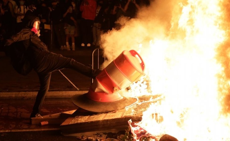 A protester kicks an object into a fire near the White House in Washington DC. Photo: 31 May 2020