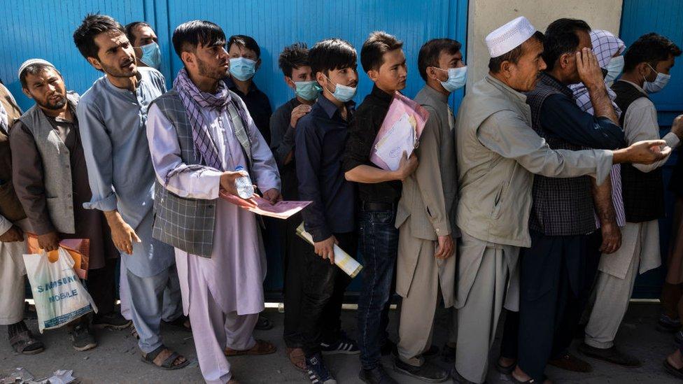 Hombres haciendo cola para una visa