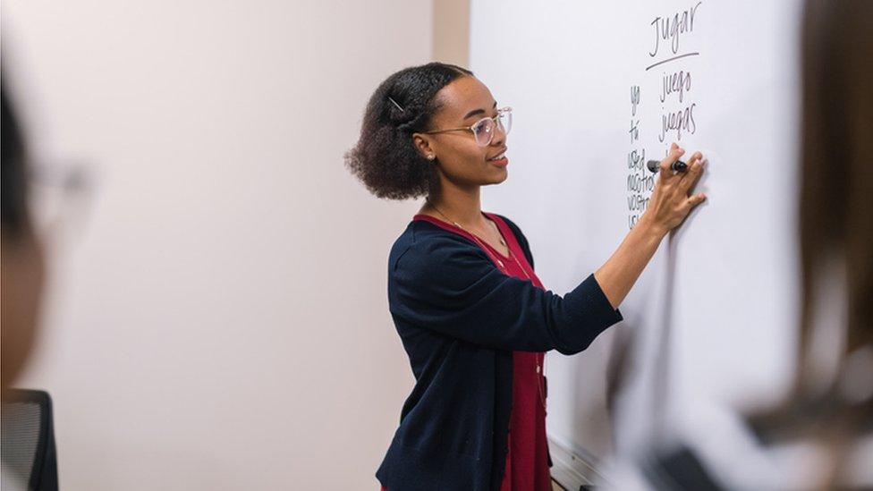 Una mujer escribe palabras en español en una pizarra.