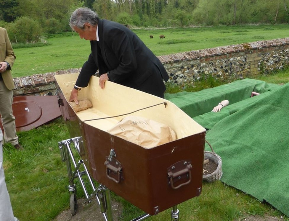 Skeletons being put in coffin