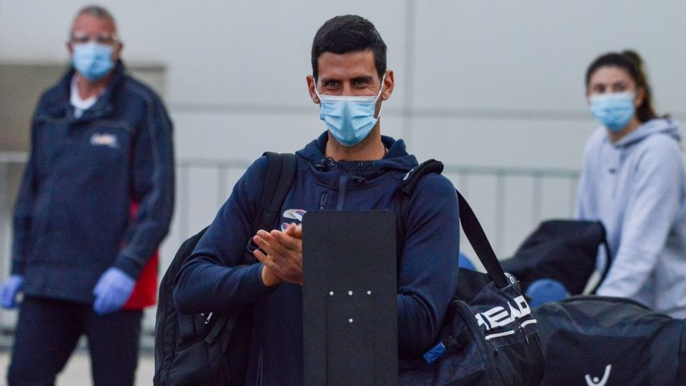 Novak Djokovic wearing a mask at Adelaide Airport on his way to hotel quarantine