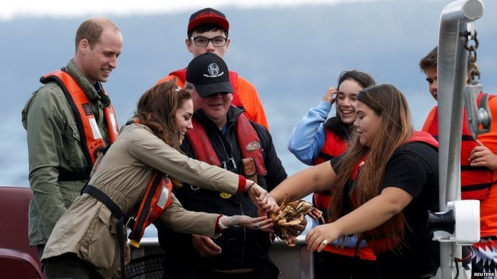 The Duchess of Cambridge handles a crab pulled from a trap in the water while fishing with Prince William during a visit to Haida Gwaii, Canada