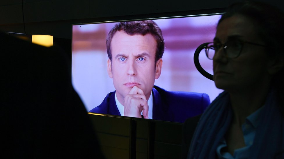 Emmanuel Macron is pictured on a television screen backstage, seconds before the start of the live debate broadcast