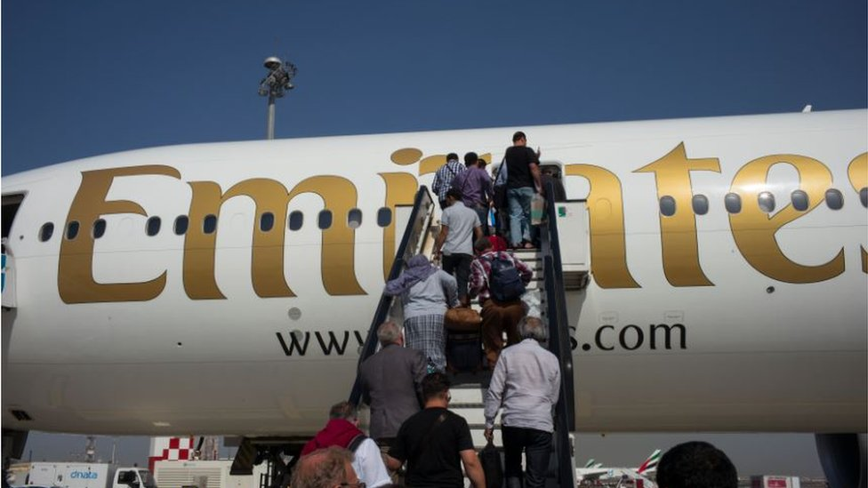 Air passengers climb stairs to an Emirates Airlines Boeing 777 passenger jet departing to Kabul from Dubai