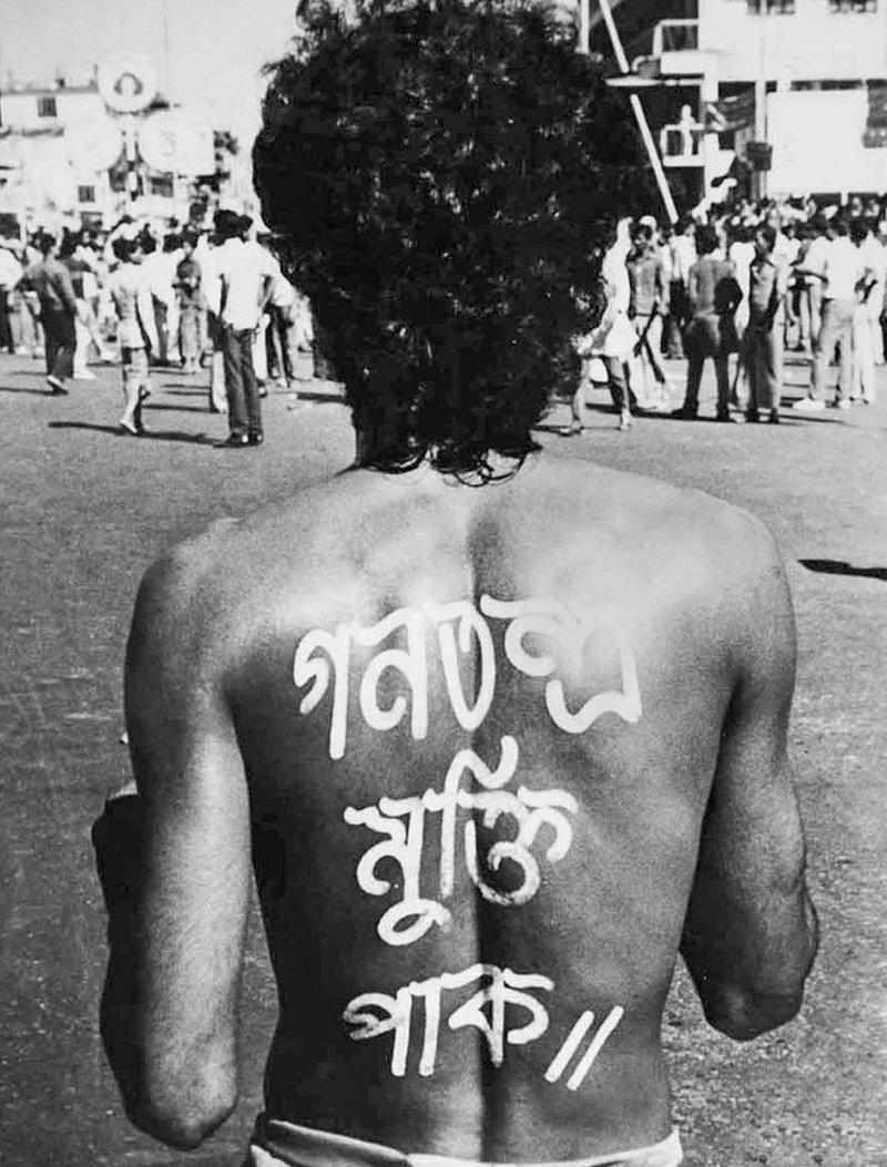 Nur Hossain de espaldas con las letras pintadas