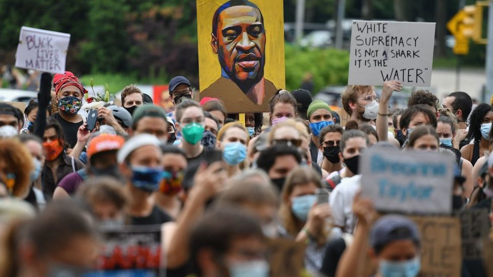 Protesters in June hold up a poster of George Floyd, who was killed by police in May