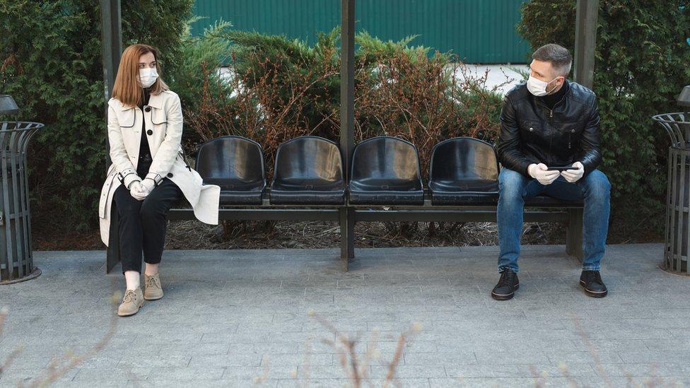 Hombre y mujer sentados a dos metros de distancia.