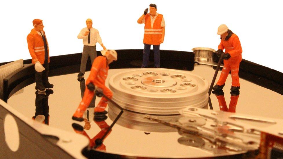Trabajadores en miniatura trabajando en el disco duro de una computadora.