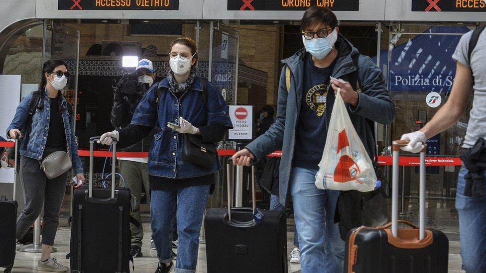 مسافرون يرتدون الكمامات الطبية في محطة القطار في نابولي