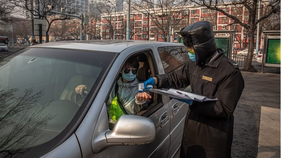 A security guard wearing a protective face mask checks body temperature of a driver at the entrance to a parking at residential area of Sanlitun in Beijing, China, 11 February 2020.