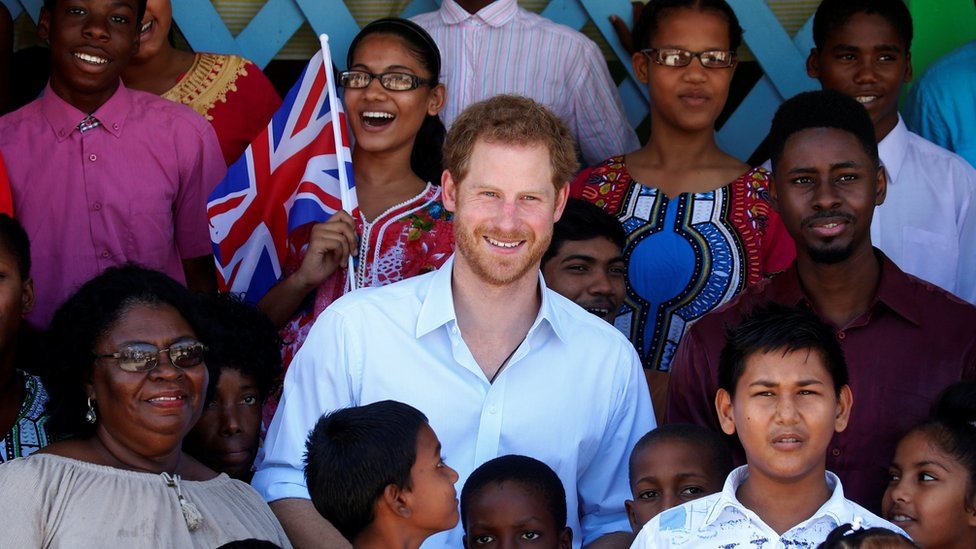 Prince Harry poses for a photo with some of the children at Joshua House Children's Center in Georgetown, Guyana