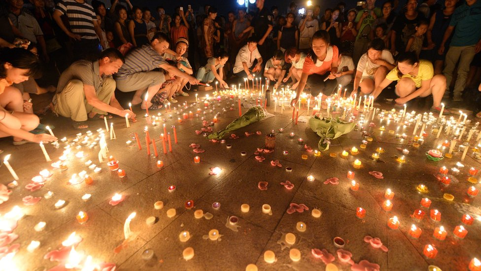 People lay candles on the ground as part of a vigil for the victims of the Kunshan blast
