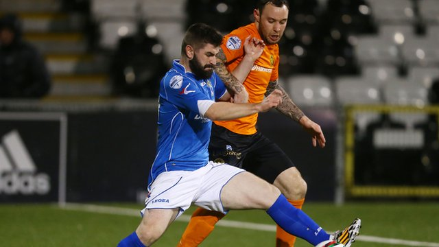 Dungannon's Cormac Burke battles with Carrick's Andrew Doyle at Seaview