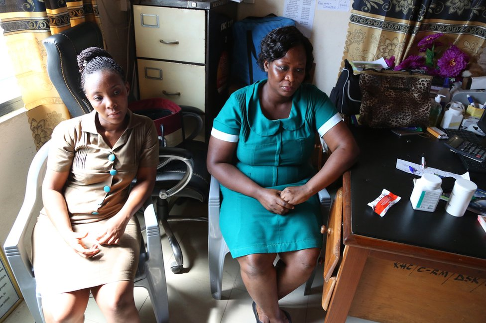 Beatrice Amponfi and Joy Glii sit inside their clinic next to a desk