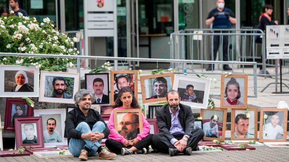 عرض نشطاء مناهضون للأسد صورا للضحايا خارج المحكمة