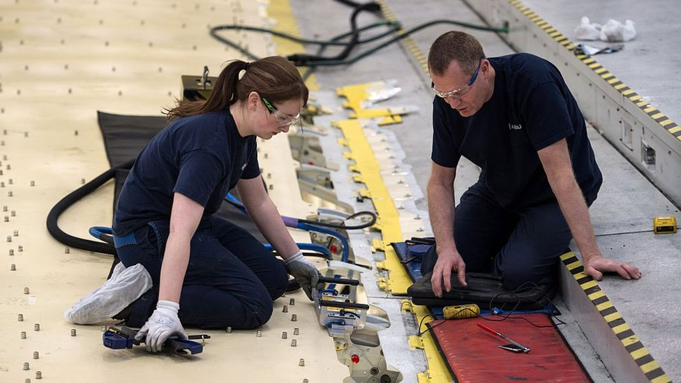 Airbus employees construct a wing for an Airbus A350 aircraft at Airbus' wing production plant near Broughton in north-east Wales