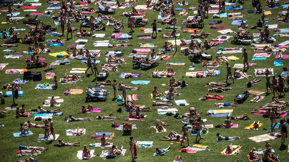 People sunbathe in a park in Prague as temperatures reach 38C in parts of the Czech Republic, 1 August 2017