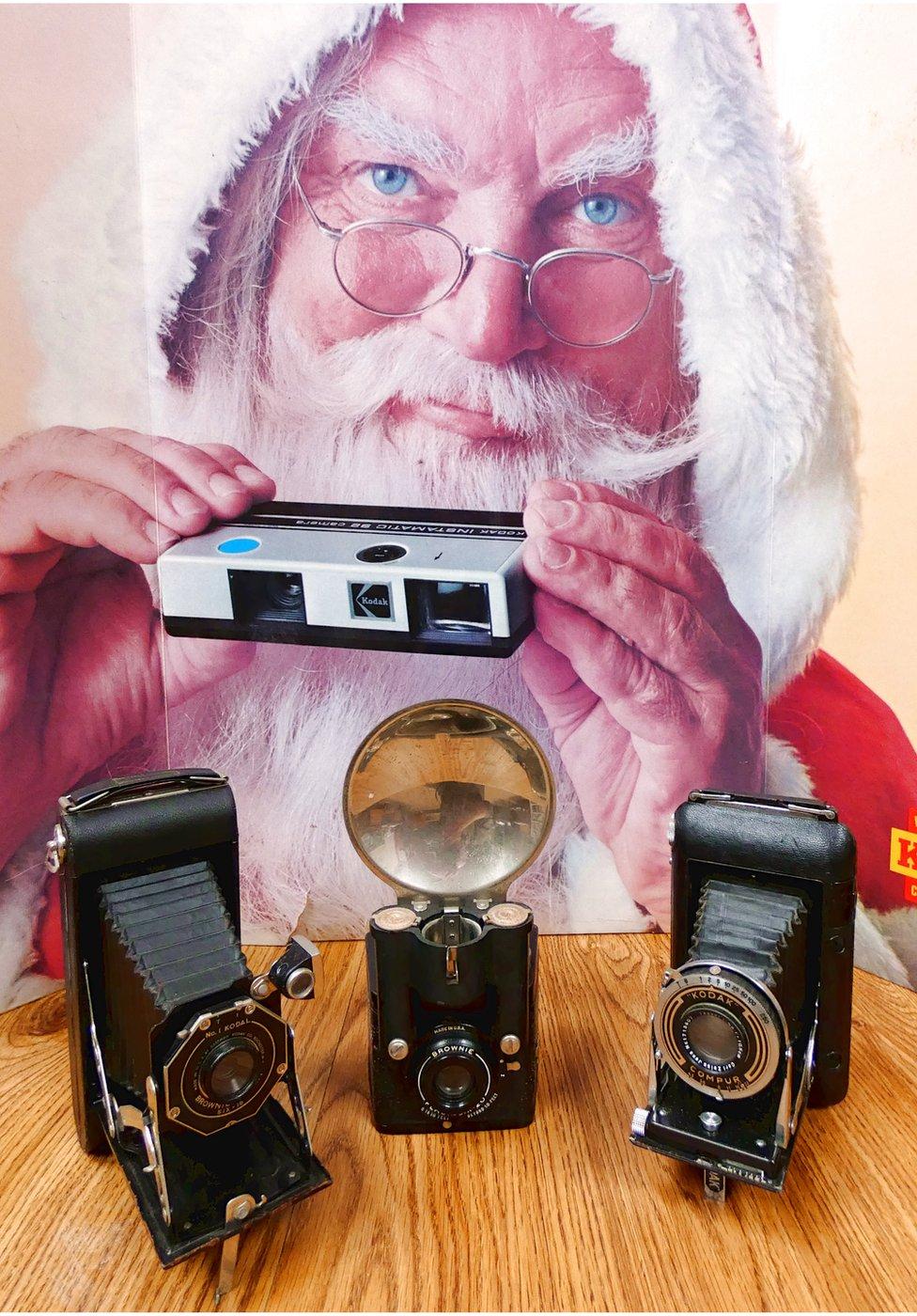 backdrop: advert for Kodak instamatic camera. Foreground, left to right: No.1 Kodal, Brownie Pliant, Six-16 folding camera (USA); Brownie Flash, Six-20, c.1941; Kodak Regent, Compur shutter, Zeiss Tessar lens, folding camera, c.1935-39 (Germany)
