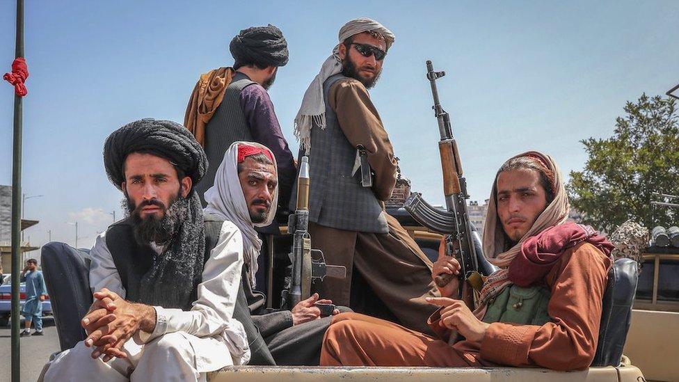 Combatientes talibanes son vistos en la parte trasera de un vehículo en Kabul, Afganistán, 16 de agosto de 2021.