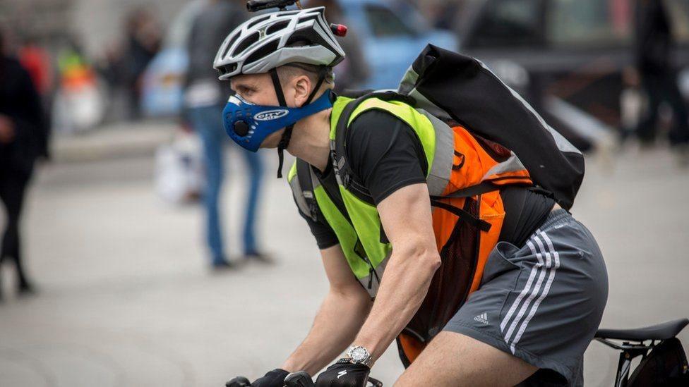 رياضي يلبس كمامة بينما يقود دراجة