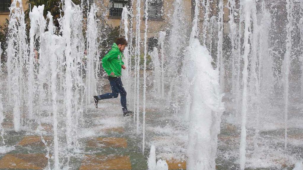 A young man runs through water fountains in Sheffield.