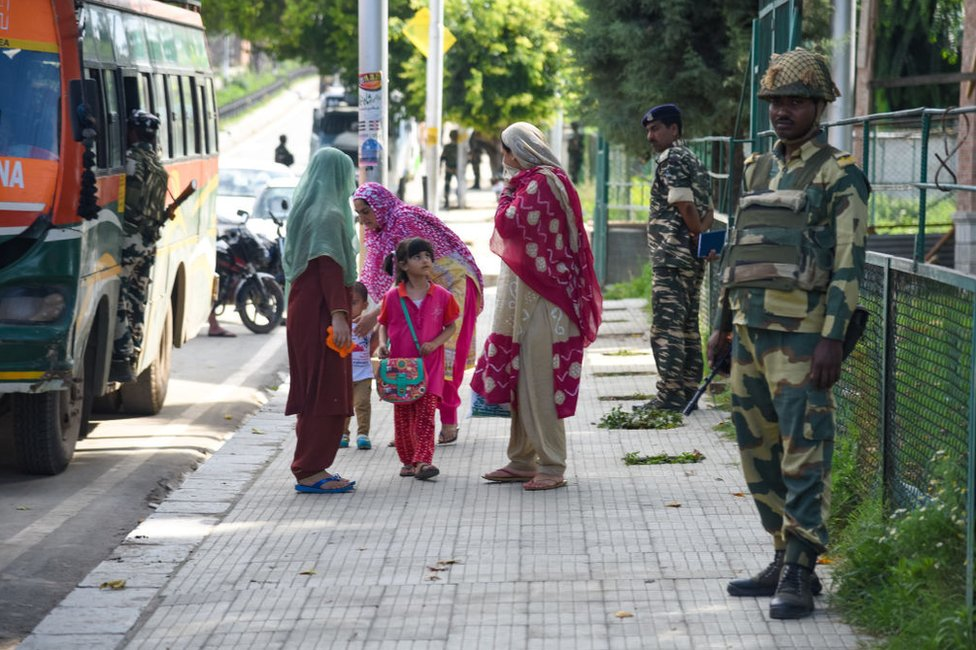 Kashmiri residents walk next to Indian troops standing on guard in Srinagar.