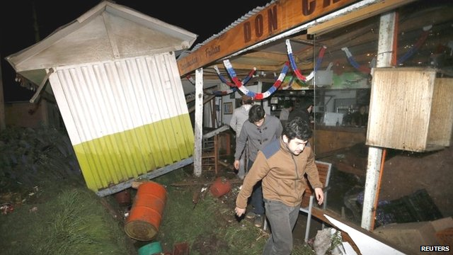 People recover items from a destroyed shop